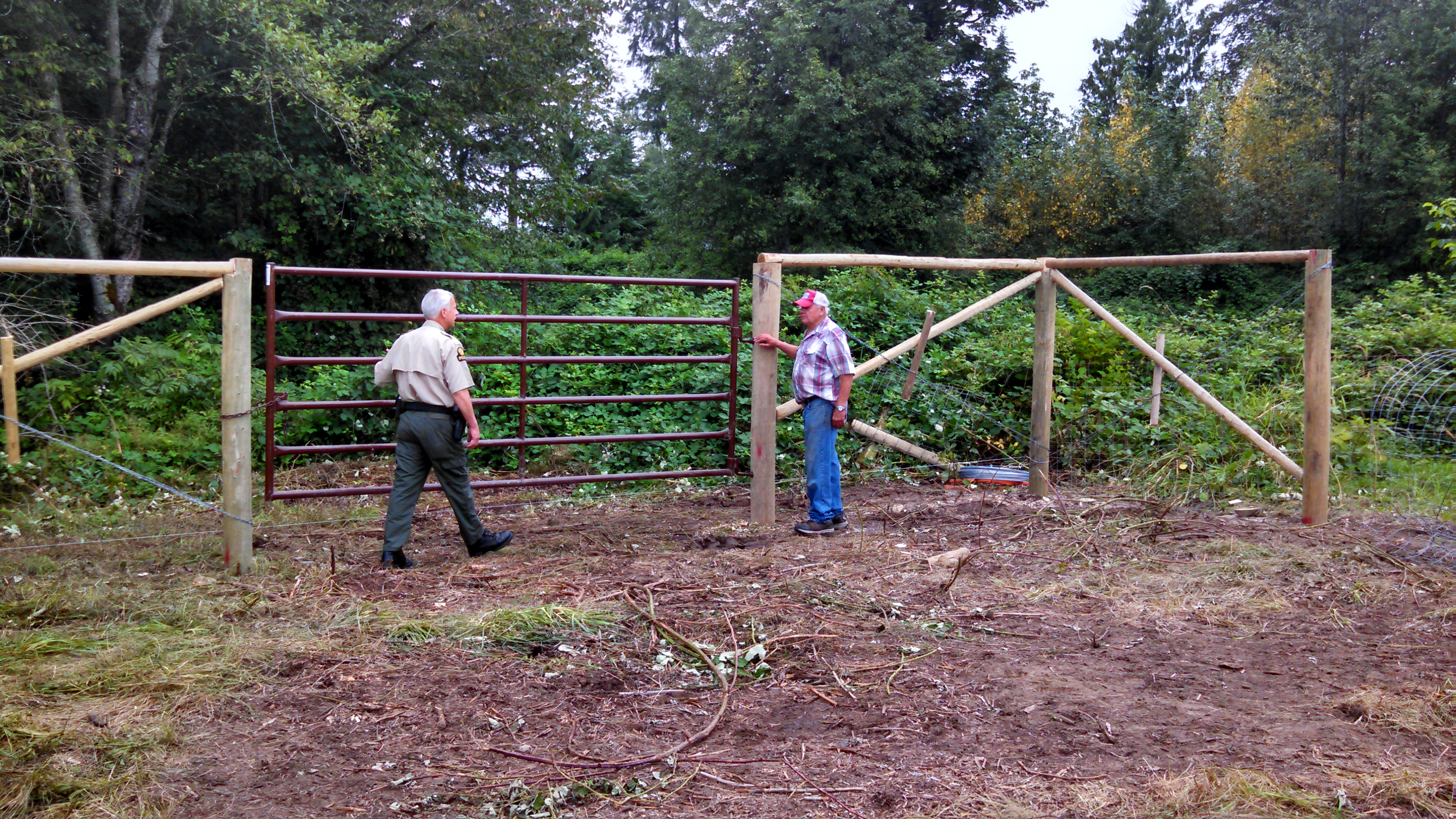 Tulalip Tribes Natural Resources Department news link to Tribes Minimize Elk Damage with Cost Effective Fence with image of two people by high fence with gate